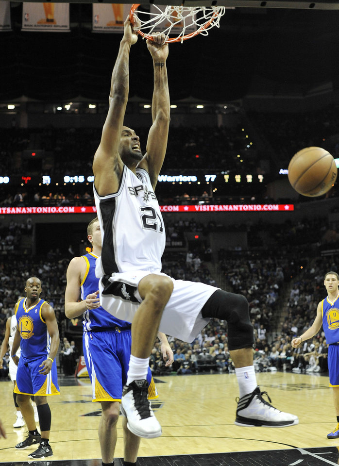 San Antoni Spus forward Tim Duncan follows through on a dunk in front of Golden State Warriors forward David Lee during the second half of an NBA basketball game on Friday, Jan. 18, 2013, in San Antonio. The Spurs won 95-88. (AP Photo/Bahram Mark Sobhani)
