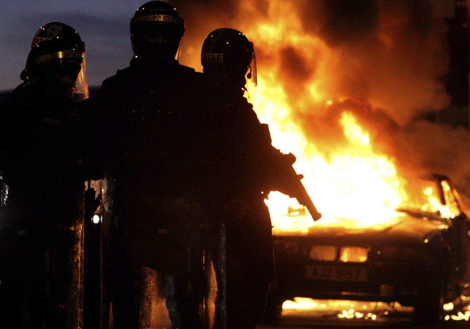 Photo - Riot police stand next to a burned out car after Loyalist protesters attacked police lines, in east BelfastNorthern Ireland, Saturday Jan. 12, 2013. Police used water cannons as four officers were injured during sectarian clashes between loyalists and republicans in east Belfast, Saturday. Trouble flared after a city centre demonstration against the council's decision to limit the number of days the Union flag is flown from City Hall (AP Photo/Paul Faith/PA) UNITED KINGDOM OUT