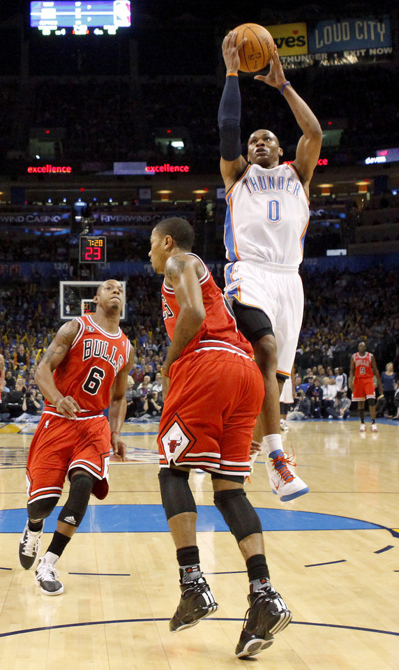 Photo - Oklahoma City's Russell Westbrook goes past Chicago's Derrick Rose and Keith Bogans, left, during the NBA basketball game between the Oklahoma City Thunder and the Chicago Bulls in the Oklahoma City Arena on Wednesday, Oct. 27, 2010. Photo by Bryan Terry, The Oklahoman