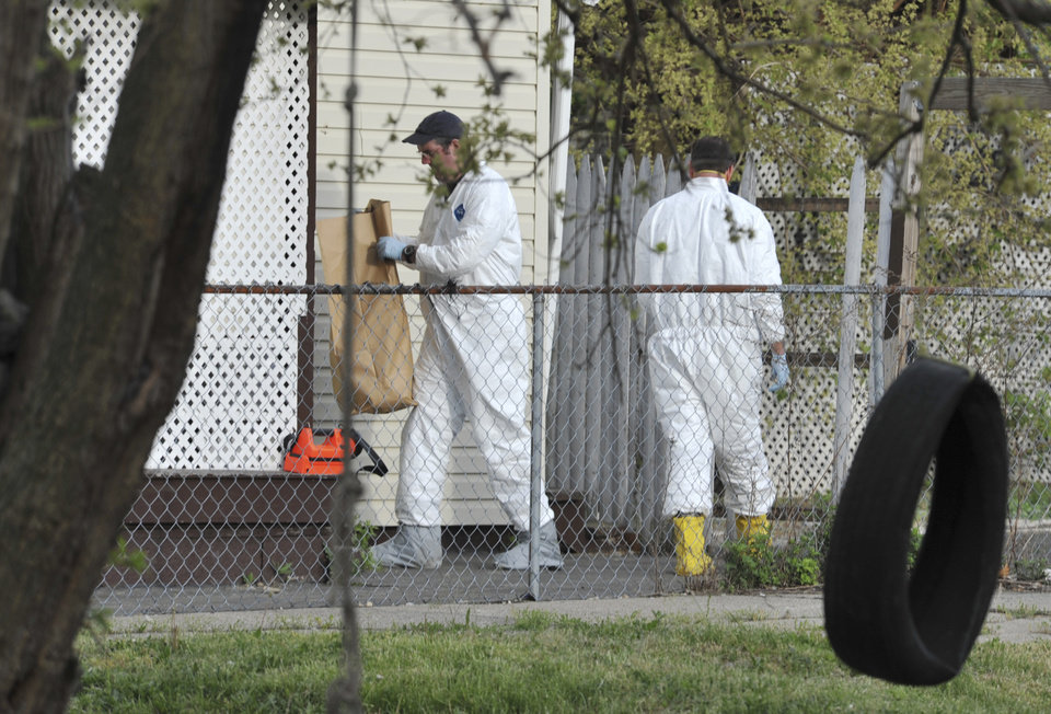 Photo - A member of the FBI evidence response team carries out a bag after searching a house near the home where three women were held Wednesday, May 8, 2013, in Cleveland. Amanda Berry, 27, Michelle Knight, 32, and Gina DeJesus, about 23, had apparently been held captive in the house nearby since their teens or early 20s, police said. (AP Photo/Roadell Hickman)