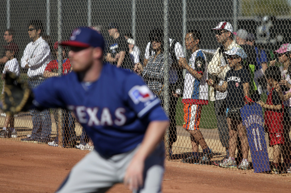 Photo - Texas Rangers pitcher Robbie Ross waits for a throw during warm ups as fans line the fence watching the team during spring training baseball practice, Monday, Feb. 17, 2014, in Surprise, Ariz. (AP Photo/Tony Gutierrez)