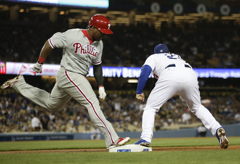 Photo - Los Angeles Dodgers first baseman Adrian Gonzalez, right, fields the throw for the out on Philadelphia Phillies' Marlon Byrd during the third inning of a baseball game on Tuesday, April 22, 2014, in Los Angeles. (AP Photo/Jae C. Hong)