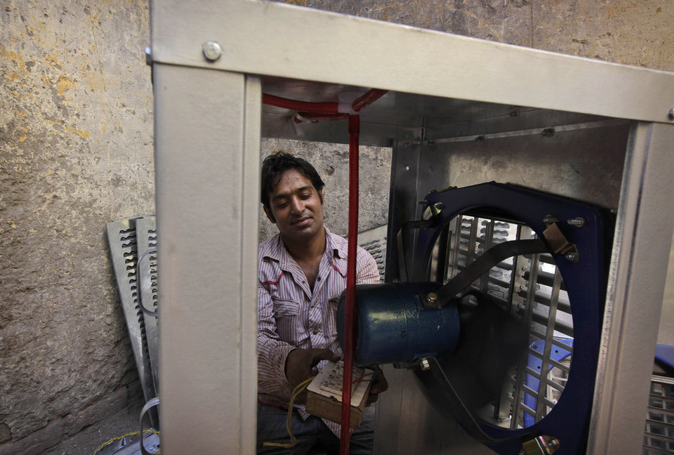 An Indian worker tests a desert cooler at a workshop, as temperatures rise to over 40.8 degrees Celsius (105 degrees Fahrenheit) in New Delhi, India, Wednesday, May 8, 2013. The demand for desert coolers increases in summer because of their efficiency coupled with affordability. (AP Photo/Manish Swarup)