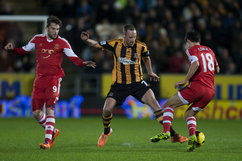 Photo - Hull City's David Meyler, center, loses the ball to Southampton's Jack Cork, right, as Jay Rodriguez looks on during their English Premier League soccer match at the KC Stadium, Hull, England, Tuesday Feb. 11, 2014. (AP Photo/Jon Super)