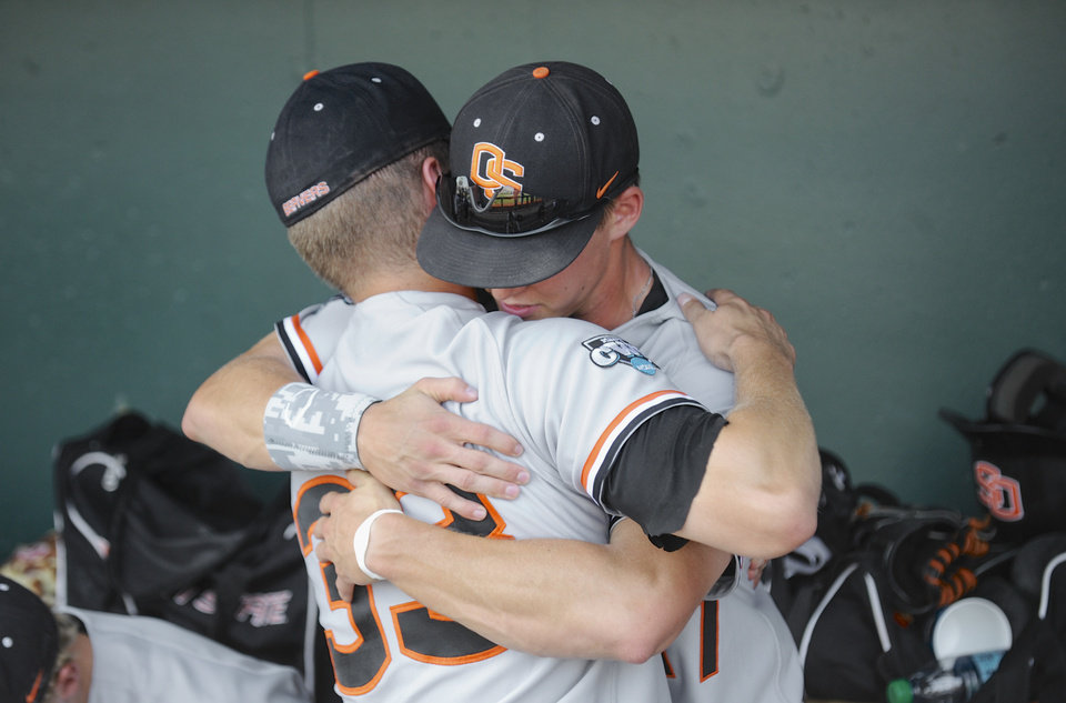 Photo - Oregon State's Ryan Barnes (33) and Joey Jansen hug after losing 4-1 to Mississippi State in an NCAA College World Series baseball game in Omaha, Neb., Friday, June 21, 2013. Mississippi State advances to the championship series and Oregon State is eliminated. (AP Photo/Francis Gardler)