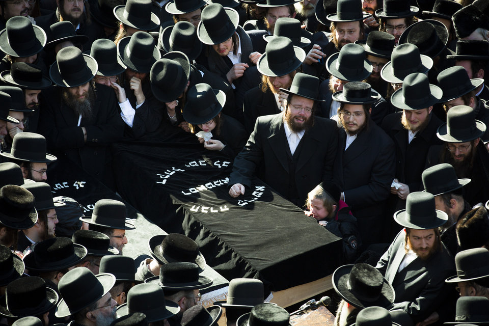 Photo - Members of the Satmar Orthodox Jewish community congregate for the funeral of two expectant parents who were killed in a car accident, Sunday, March 3, 2013, in the Brooklyn borough of New York. A driver struck the car the couple were riding in early Sunday morning, killing both parents while their baby, who was born prematurely, survived and is in critical condition. (AP Photo/John Minchillo)