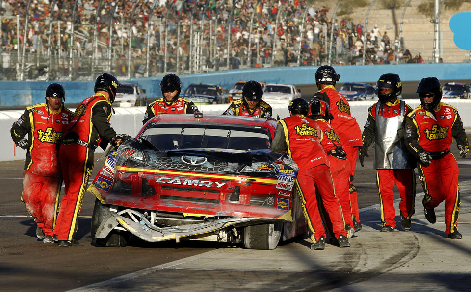 Clint Bowyer's pit crew pushes his car into the garage area after a crash with Jeff Gordon during thea NASCAR Sprint Cup Series auto race at Phoenix International Raceway, Sunday, Nov. 11, 2012, in Avondale, Ariz. (AP Photo/Ross D. Franklin)