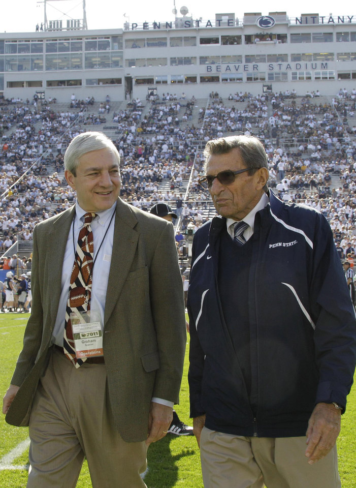 "FILE - In this Oct. 8, 2011, file photo Penn State president Graham Spanier, left, and head football coach Joe Paterno talk before an NCAA college football game against Iowa in State College, Pa. Spanier is accused of perjury, endangering children and other charges in the Jerry Sandusky molestation scandal. According to online court records charges were filed, Thursday, Nov. 1, 2012, against Penn State\'s ex-president and two other administrators in what prosecutors called ""a conspiracy of silence."