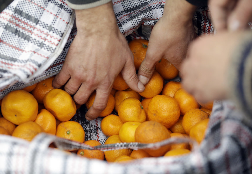 Photo - People buys some of Mukhmunad Ashabokova's tangerines off of her cart at the Abkhazian border Wednesday, Feb. 5, 2014, near Sochi, Russia. Most days in the tangerine season, she rolls her squat cart loaded down with the fruit across the bridge over Psou River from her garden about two miles inside Abkhazia. (AP Photo/Morry Gash)