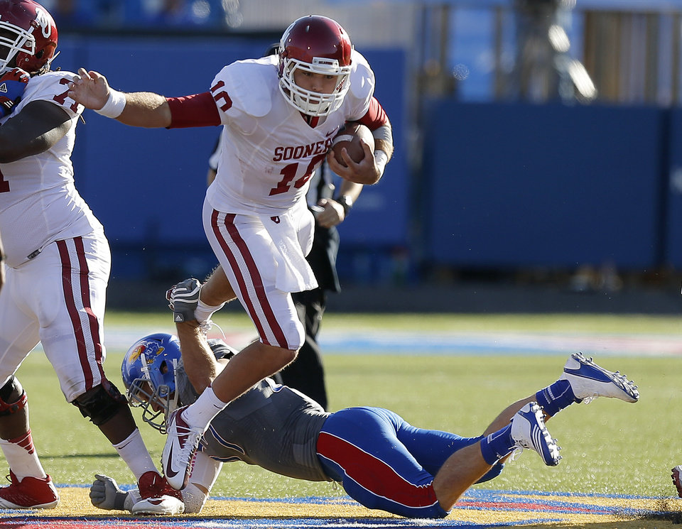 OU's Blake Bell (10) leaps over KU's Jake Love (57) during the college football game between the University of Oklahoma Sooners (OU) and the University of Kansas Jayhawks (KU) at Memorial Stadium in Lawrence, Kan., Saturday, Oct. 19, 2013. Oklahoma won 34-19. Photo by Bryan Terry, The Oklahoman