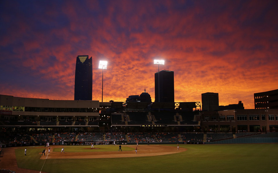 Photo - The sun sets during a Big 12 Tournament baseball game between Oklahoma State University and the University of Texas at Chickasaw Bricktown Ballpark in Oklahoma City, Saturday, May 24, 2014. Photo by Bryan Terry The Oklahoman