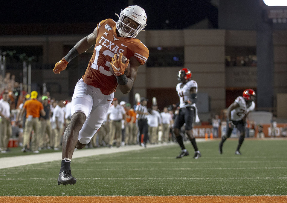Photo - Texas wide receiver Brennan Eagles (13) runs into the end zone after catching a pass against Oklahoma State during an NCAA college football game Saturday, Sept. 21, 2019, in Austin, Texas. (Nick Wagner/Austin American-Statesman via AP)