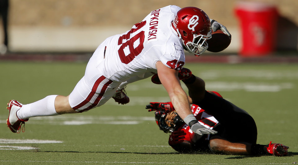 Photo - Oklahoma's Aaron Ripkowski (48) leaps past Texas Tech's Justis Nelson (31) during a college football game between the University of Oklahoma Sooners (OU) and the Texas Tech Red Raiders at Jones AT&T Stadium in Lubbock, Texas, Saturday, November 15, 2014.  Photo by Bryan Terry, The Oklahoman