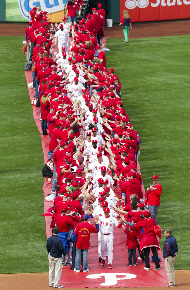 Photo - Philadelphia Phillies' manager Ryne Sandberg leads his team from centerfield while surrounded by fans for an opening day baseball game between the Milwaukee Brewers and Philadelphia Phillies in Philadelphia, Tuesday, April 8, 2014. (AP Photo/Chris Szagola)