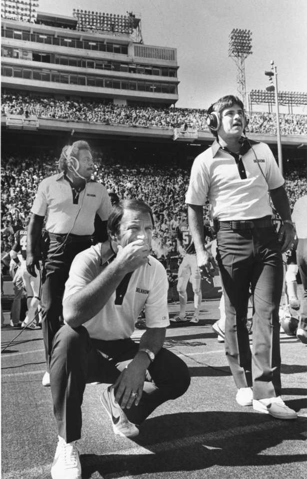 """Photo -  """"OU (college football) coaches Barry Switzer (kneeling), Wendell Mosley (left) and Bob Jones find the scene in the Cotton Bowl sometimes inspiring, sometimes depressing, and always engrossing."""" Staff photo by Paul B. Southerland taken 10-11-80; photo ran in the 10-12-80 Daily Oklahoman."""