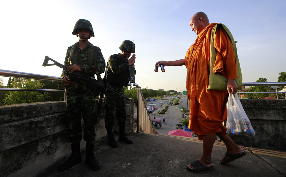 Photo - A Buddhist monk offers energy drink to Thai soldiers guarding a pedestrian overfly near the site where pro-government demonstrators stage a rally on the outskirts of Bangkok, Thailand Tuesday, May 20, 2014. As Thailand finishes its first day under martial law, there are some questions that the military action raises. Many wonder if the arrival of soldiers in the streets of Bangkok constitutes a military coup, and how it affects people living in the Thai capital or visiting.  (AP Photo/Wason Wanichakorn)