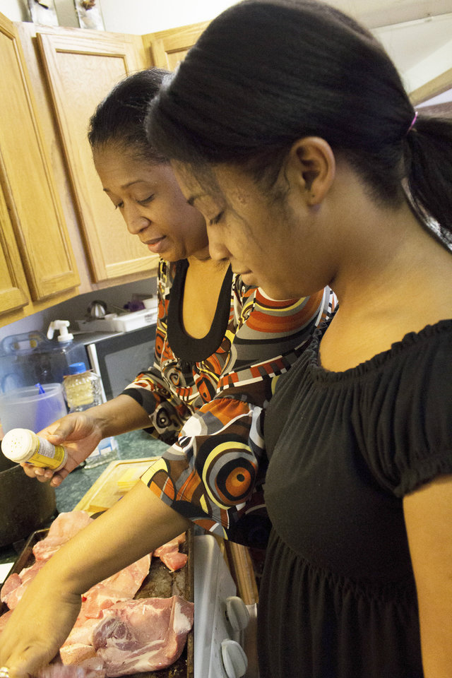 Keta cooks with her 14-year-old daughter Maeahja, who, along with her two siblings, is covered by government-provided insurance. Photo by Heather Brown for The Oklahoman