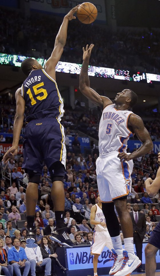 Photo - Utah Jazz's Derrick Favors (15) blocks a shot by Oklahoma City Thunder's Kendrick Perkins (5) during the NBA basketball game between the Oklahoma City Thunder and the Utah Jazz at Chesapeake Energy Arena on Wednesday, March 13, 2013, in Oklahoma City, Okla. Photo by Chris Landsberger, The Oklahoman