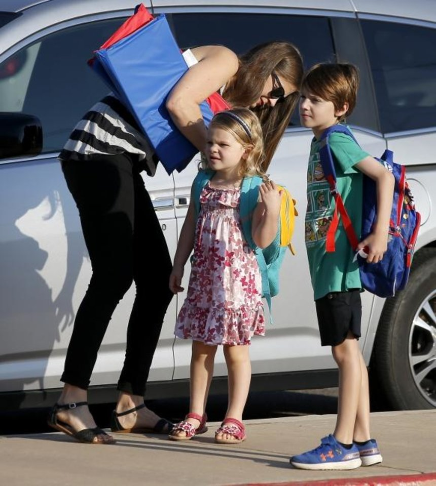 Photo -  Katie Clark helps her daughter Mallory, 4, with her backpack Friday as she walks with her son Max, 8, to Chisholm Elementary School for the first day of school in Edmond. [Bryan Terry/The Oklahoman]