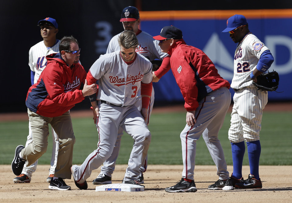 Photo - Washington Nationals' Bryce Harper, third from left, is helped off the field after being hit while being tagged out at second base during the second inning of the baseball game against the New York Mets on opening day at Citi Field in New York, Monday, March 31, 2014.  (AP Photo/Seth Wenig)