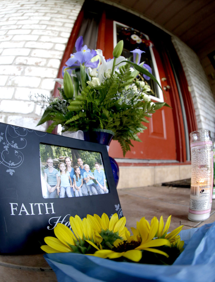 Photo - A photograph, flowers and candles are left on the porch where a fatal home shooting took place Thursday, July 10, 2014, in Spring, Texas. The Harris County Sheriff's Office says Ronald Lee Haskell was booked Thursday on a capital murder/multiple murders charge and held without bond. Authorities believe Haskell fatally shot two adults and four children on Wednesday night and critically wounded a 15-year-old girl, who called 911.  (AP Photo/David J. Phillip)