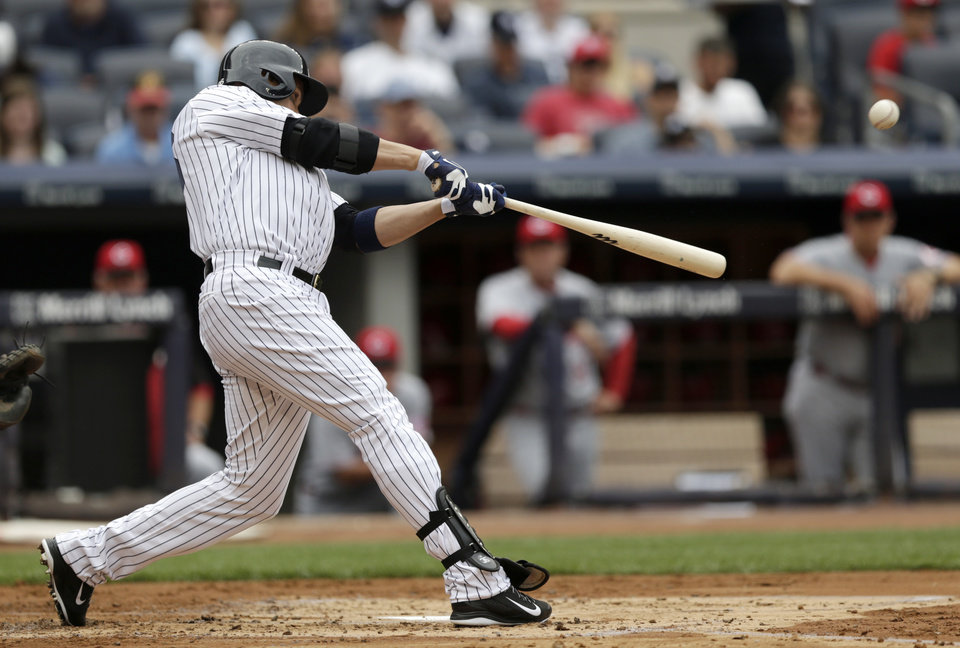 Photo - New York Yankees' Carlos Beltran connects for a home run off Cincinnati Reds starting pitcher Alfredo Simon during the second inning of a baseball game, Saturday, July 19, 2014, at Yankee Stadium in New York. (AP Photo/Julio Cortez)