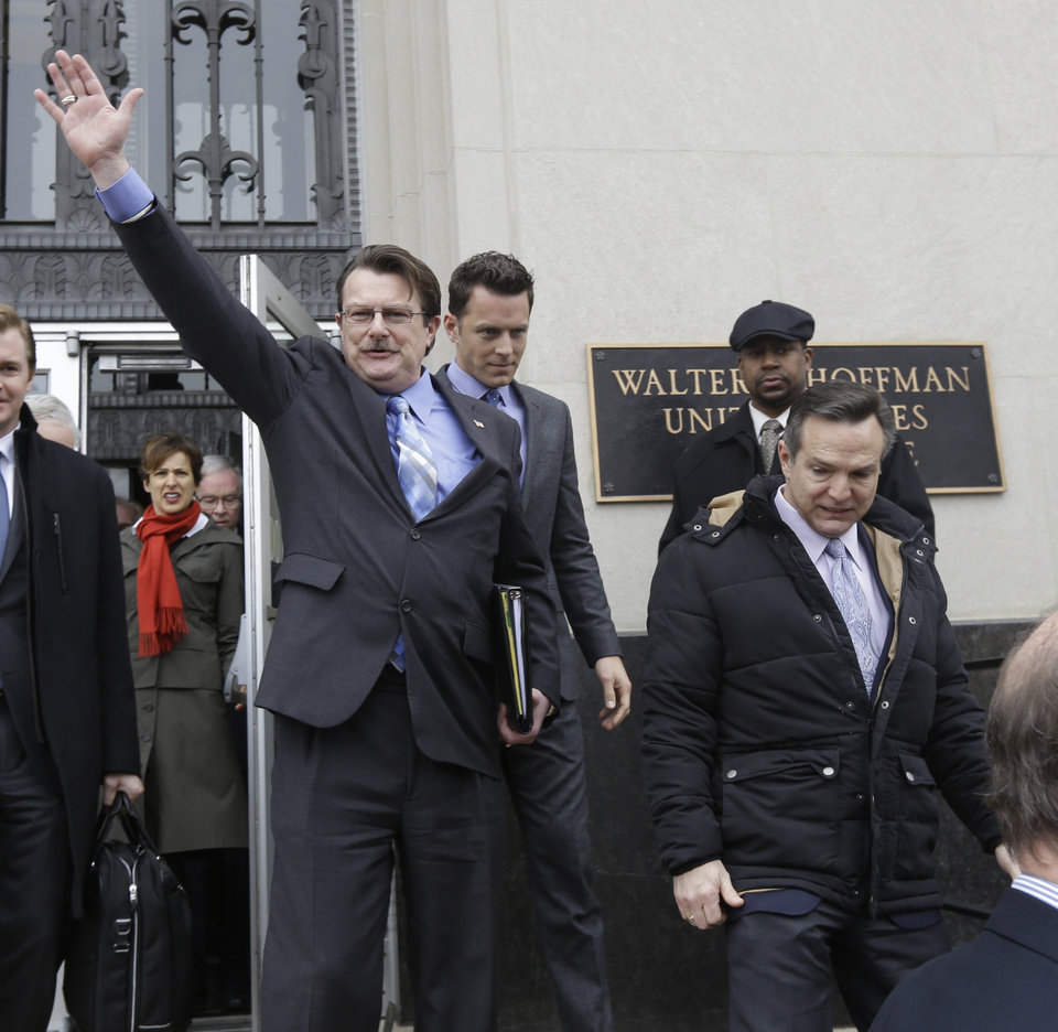 Photo - Plaintiff in the Bostic v. Rainey case,  Tony London, waves to the crowd as he and his partner, Tim Bostic, right, leave Federal Court after a hearing on Virginia's ban on gay marriage in Norfolk, Va., Tuesday, Feb. 4, 2014.    A federal judge heard arguments on whether Virginia's ban on gay marriage is unconstitutional. (AP Photo/Steve Helber)