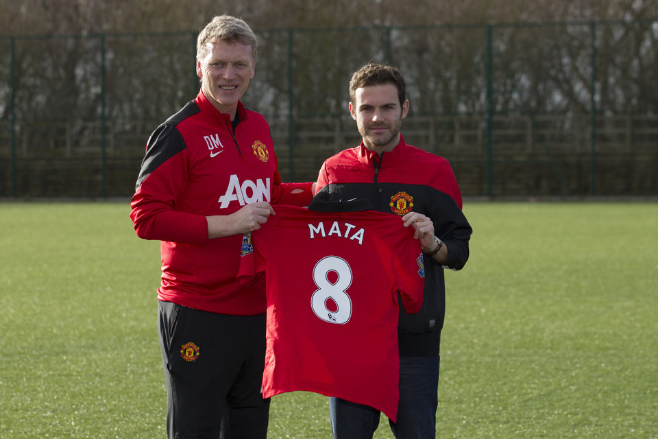 Photo - Manchester United's new signing Juan Mata, right, displays his new shirt alongside manager David Moyes before a press conference at the team's Carrington training ground, Manchester, England, Monday, Jan. 27, 2014. With Manchester United in danger of missing out on the Champions League next season, Juan Mata's arrival at Old Trafford for a club record fee of 37.1 million pounds ($61.2 million) is certainly an emergency move. But it also marks the first step in the rebuilding process of England's most titled club. After a botched transfer campaign last summer that was followed by the club's lackluster first half of the season, United now looks determined to allow manager David Moyes the opportunity to build his own team.(AP Photo/Jon Super)