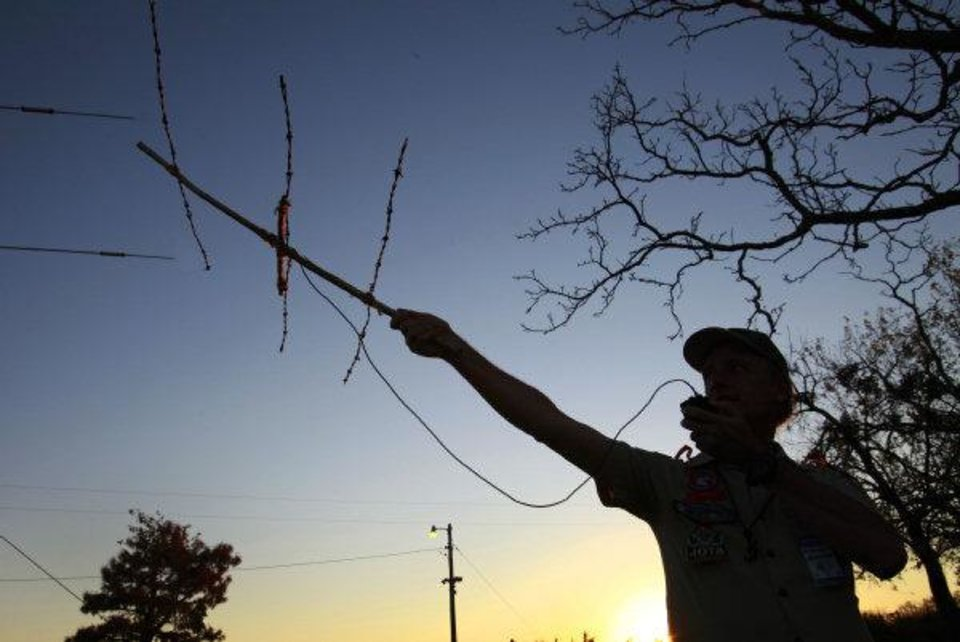 Photo - Doug Cook with the Radio Scouter Group tries to contact the International Space Station with a barb wire antena and a 5 wat radeo last weekend during the 54th Jamboree-On-The -Air at  John Nichols Scout Ranch.  David McDaniel - THE OKLAHOMAN