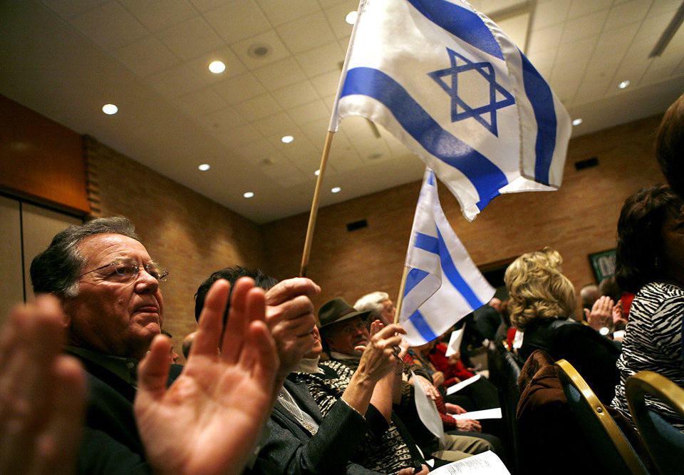 Jerry McCurry, of Luther, Okla., who is director of a group called Christians United for Israel, waves an Israeli flag during a song before a Community Gathering at Temple B'nai Israel in Oklahoma City on Monday, Jan. 12, 2009. By John Clanton, The Oklahoman