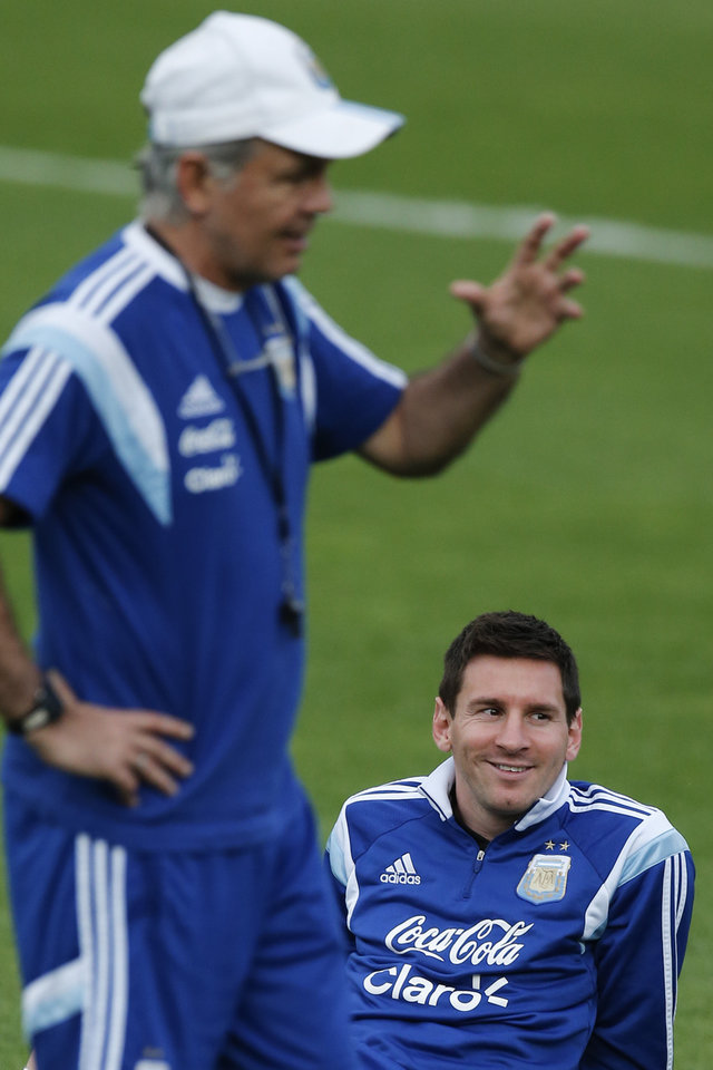 Photo - Argentina's Lionel Messi, bottom, listens to Argentina's head coach Alejandro Sabella, left, during a training session in Vespesiano, near Belo Horizonte, Brazil, Wednesday, July 2, 2014. On Saturday, Argentina will face Belgium in their World Cup soccer match quarterfinal. (AP Photo/Victor R. Caivano)