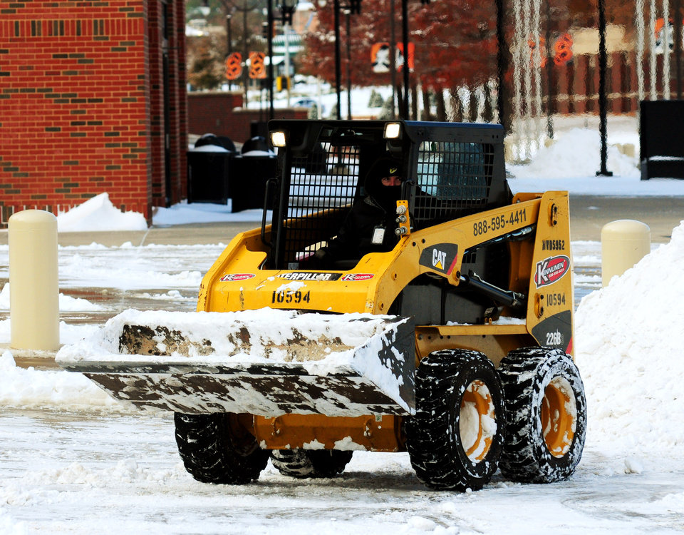 A stadium worker outside of Boone Pickens Stadium drives a small tractor to clear a snow filled parking lot on Dec. 6, 2013. After Stillwater received heavy snowfall on Thursday and Friday, ahead of Saturday's bedlam football game, the Oklahoma State athletic department was forced to clear the snow quickly for the game. KT King/For the Tulsa World