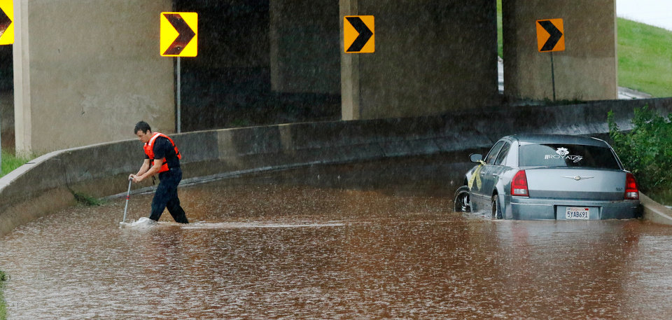 Photo - An Oklahoma City firefighter uses a tool to prevent him from stepping into deep water as he makes his way back to a a high area after checking for occupants inside this stranded car on the northbound ramp to I-235 at NW 23 Street. Brief periods of heavy rain caused road flooding and created hazardous driving conditions around 7 pm Saturday, May 23, 2015.  Oklahoma City police used their vehicles to barricade all directions of traffic at NW 23 and Broadway, preventing vehicles from driving into high and rushing water. Photo by Jim Beckel, The Oklahoman.