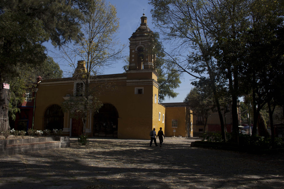 Photo -   People walk in the Santa Catarina square in Coyoacan, a former village south of central Mexico City, Tuesday, Nov. 20, 2012. A former village south of central Mexico City, this charming neighborhood of cobblestone streets, brightly painted colonial houses and tree-shaded plazas was home to Frida Kahlo, Diego Rivera and hundreds of other artists over the decades. (AP Photo/Alexandre Meneghini)