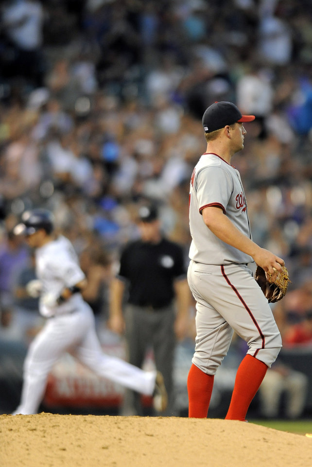 Photo - Washington Nationals starting pitcher Jordan Zimmermann looks at right field as Colorado Rockies Corey Dickerson rounds the bases after hitting a solo home run in the sixth inning of a baseball game on Tuesday, July 22, 2014, in Denver. (AP Photo/Chris Schneider)