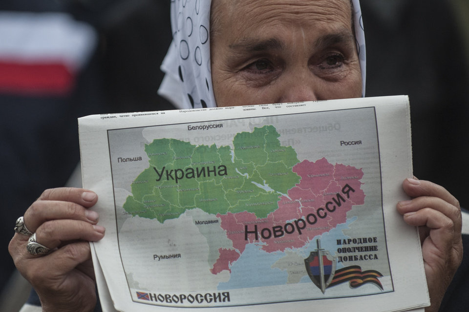Photo - A woman holds a map of Ukraine divided into two parts, the eastern carrying the name Novorossia, or New Russia, during a rally in support of peace in Donetsk, eastern Ukraine, Wednesday, June 18, 2014.  Hundreds of miners went on a protest walk through the streets of central Donetsk on Wednesday, trying to express support for a peaceful resolution to the eastern Ukraine conflict, ongoing for almost four months. (AP Photo/Evgeniy Maloletka)