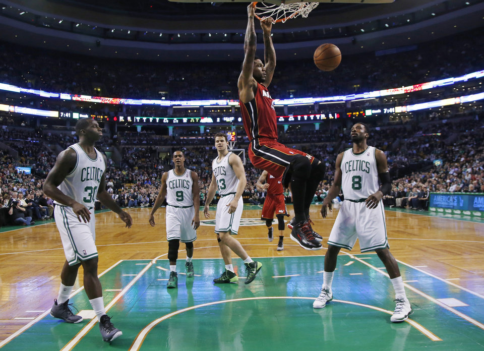 Photo - Miami Heat forward Udonis Haslem (40) dunks as Boston Celtics forward Brandon Bass (30), guard Rajon Rondo (9), center Kris Humphries (43) and forward Jeff Green (8) watch in the first quarter of an NBA basketball game in Boston Wednesday, March 19, 2014. (AP Photo/Elise Amendola)