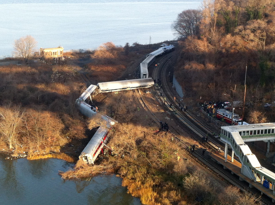 Photo - Cars from a Metro-North passenger train are scattered after the train derailed in the Bronx borough of New York, Sunday, Dec. 1, 2013. The Fire Department of New York says there are