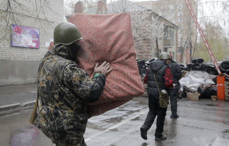 Photo - A pro-Russian gunman carries a mattress in a seized police station in the eastern Ukraine town of Slovyansk on Sunday, April 13, 2014. Pro-Moscow protesters have seized a number of government buildings in the east over the past week, undermining the authority of the interim government in the capital, Kiev. (AP Photo/Efrem Lukatsky)