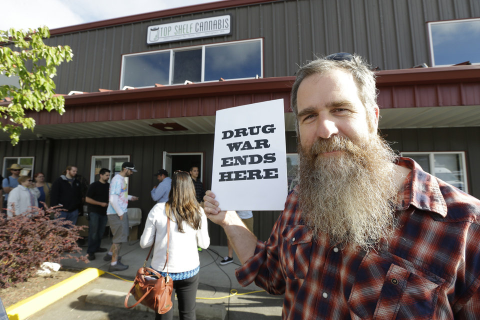 Photo - Kevin Nelson, of Bellingham, Wash., holds a sign that reads