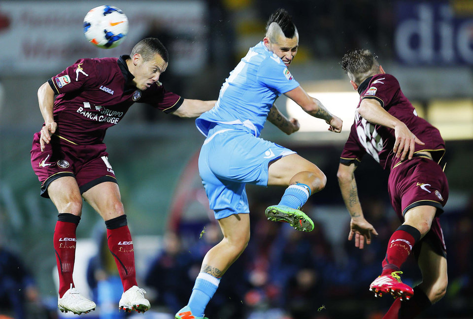 Photo - Livorno's Djamel Mesbah of Algeria, left, and teammate Andrea Coda, right, jump for the ball with Napoli's Marek Hamsik of Slovakia during a Serie A soccer match between Livorno and Napoli, in Leighorn, Italy, Sunday, March 2, 2014. (AP Photo/Francesco Speranza)le