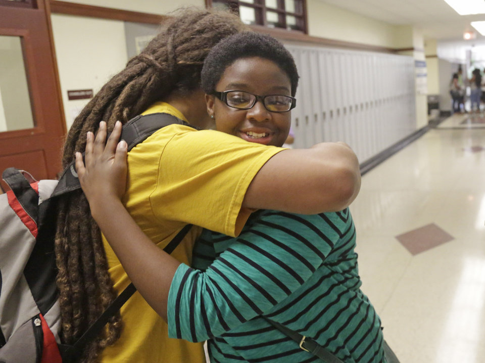 Photo - In This Aug. 29, 2014, photo Erin Nwachukwu, right, hugs her friend Yosef Smith during orientation day at Lindblom Math and Science Academy in Chicago. A new study has found that, while Americans are mistrustful of each other and institutions -- from government to corporations and the media -- young people are among the least likely age group to have confidence in those institutions, especially since the terror attacks of Sept. 11, 2001. Nwachukwu, 16, says it's been difficult for her generation to keep the faith through multiple political scandals, a recession and various shootings — including the recent shooting of a young man in Ferguson, Missouri.