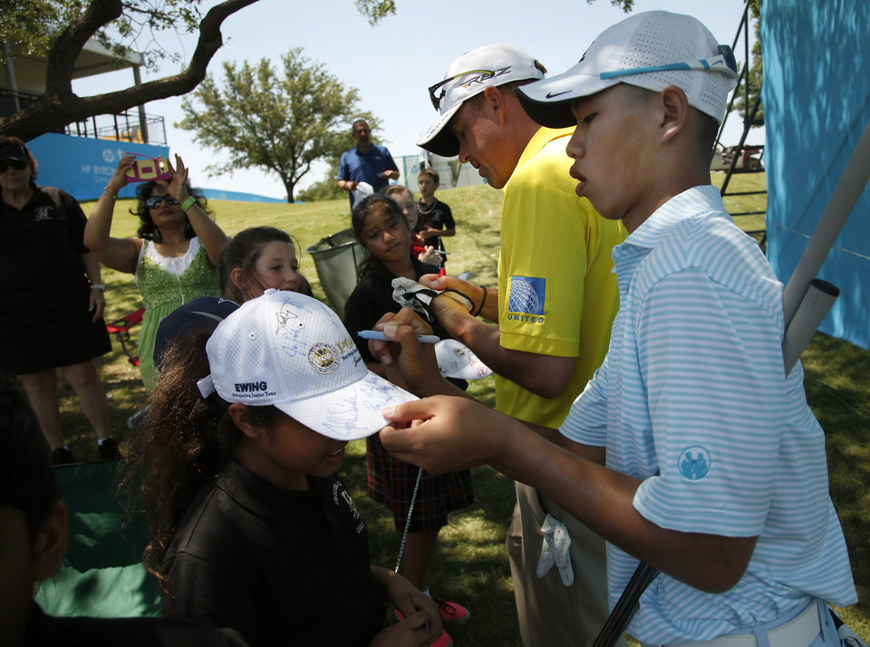 Photo - In this photo taken Tuesday, May 14, 2013, Guan Tianlang, 14, from China, and signs autographs with Matt Bettencourt sign autographs on the 17th hole during a practice round at Byron Nelson Championship golf tournament in Irving, Texas. (AP Photo/The Dallas Morning News, Brad Loper)  MANDATORY CREDIT; MAGS OUT; TV OUT; INTERNET USE AP MEMBERS ONLY; NO SALES.