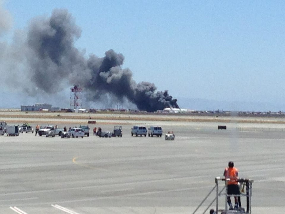 Photo - This photo provided by Krista Seiden shows smoke rising from what a federal aviation official says was an Asiana Airlines flight crashing while landing at San Francisco airport on Saturday, July 6, 2013. (AP Photo/Krista Seiden)