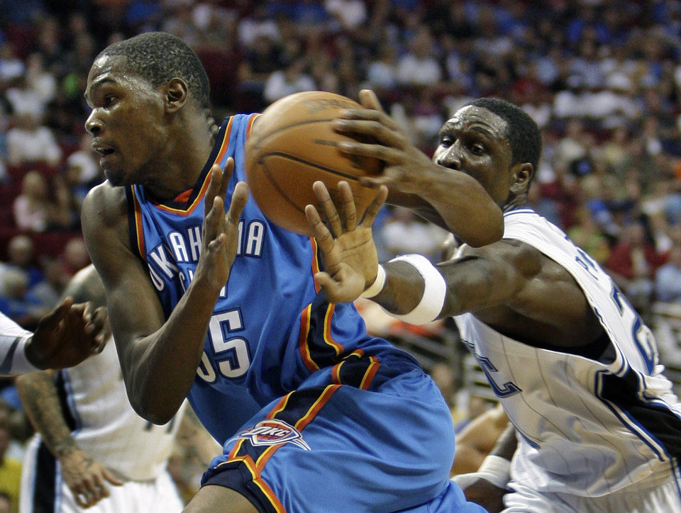 Photo - Oklahoma City Thunder forward Kevin Durant, left, drives to the basket as Orlando Magic forward Mickael Pietrus, of France, tries to steal the ball during the first half of an NBA basketball game in Orlando, Fla., Wednesday, Nov. 18, 2009. (AP Photo/John Raoux) ORG XMIT: DOA101