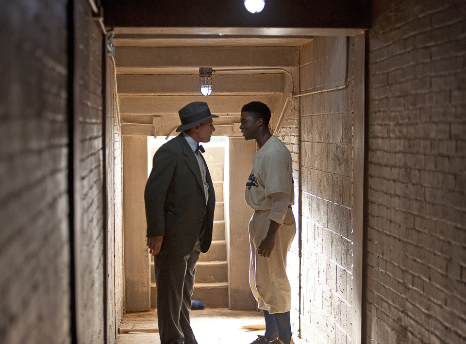 Photo - This film image released by Warner Bros. Pictures shows Chadwick Boseman as Jackie Robinson, right, and Harrison Ford as Branch Rickey in a scene from