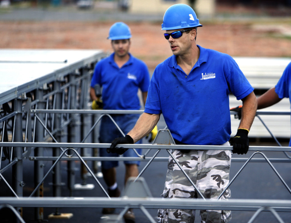 Patrick Petricca, with Serenus Johnson Portables, assembles framework for flooring as workers construct a temporary emergency room at the site where a tornado destroyed Moore Medical Center on Wednesday. PHOTO BY STEVE SISNEY, THE OKLAHOMAN <strong>STEVE SISNEY - THE OKLAHOMAN</strong>