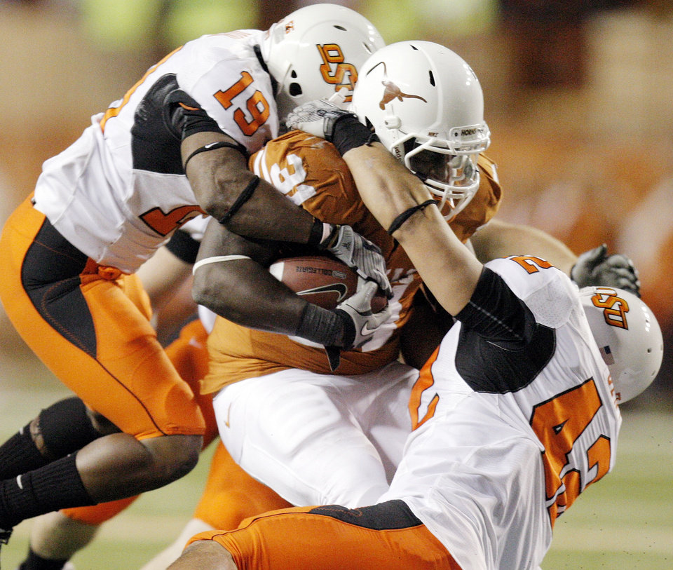 Photo - OSU's Brodrick Brown (19) and Justin Gent (42) stop Cody Johnson (31) of Texas on a carry in the second quarter during the college football game between the Oklahoma State University Cowboys (OSU) and the University of Texas Longhorns (UT) at Darrell K Royal-Texas Memorial Stadium in Austin, Texas, Saturday, November 13, 2010. Photo by Nate Billings, The Oklahoman