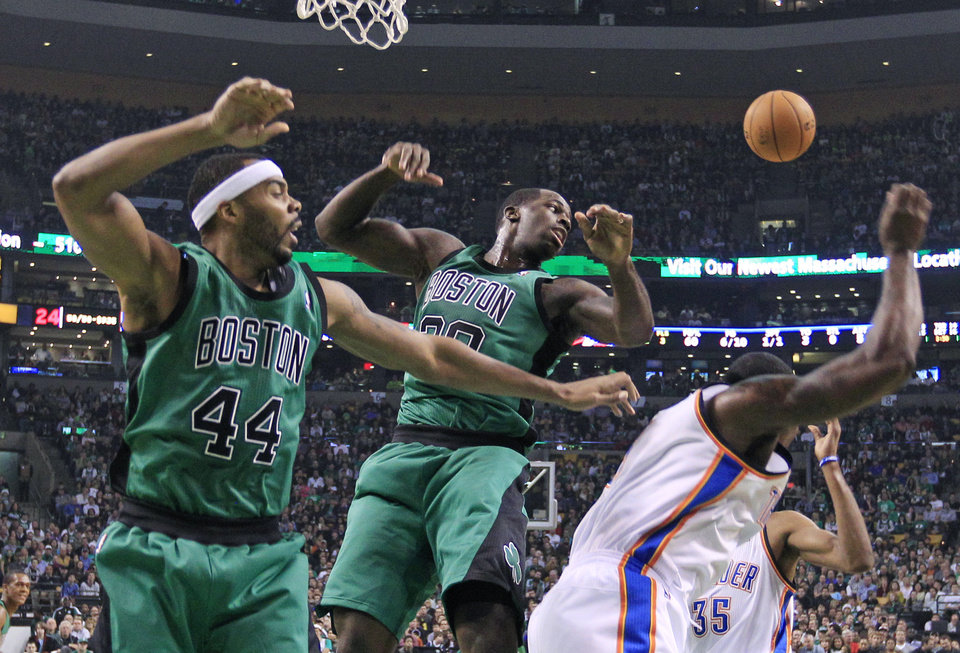 A loose rebound bounces away from Boston Celtics forwards Chris Wilcox (44) and Brandon Bass (30) as they vie under the boards with Oklahoma City Thunder center Kendrick Perkins, right, during the first half of an NBA basketball game in Boston, Friday, Nov. 23, 2012. (AP Photo/Elise Amendola)