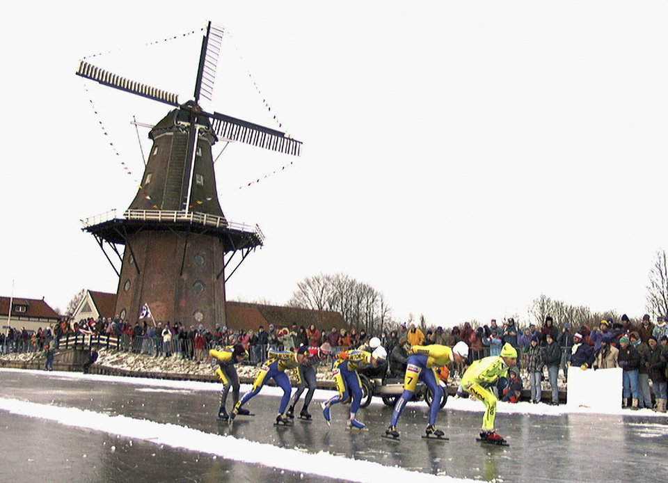 Photo - FILE - In this Jan. 4, 1997, file photo, skaters pass a windmill as some 16,000 people participate in the historic 200km skating spectacle the 'Elfstedentocht' (eleven-cities-course) in Birdaard, province of Friesland, northern Netherlands. There is nothing more mythical in Dutch sports than an age-old 11-city race skating across lakes and canals in bone-numbing cold from dawn to dusk. No wonder the Netherlands is the greatest speedskating nation in the world. And with Sven Kramer and Ireen Wust leading the way on big oval in Sochi they are bent on proving it again.  (AP Photo/Dimitri Georganas, File)